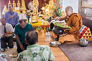 "11 MARCH 2012 - CHANDLER, AZ:      The Abbot at Wat Pa in Chandler, AZ, collects food in the ""bot"" or ordination hall during Makha Bucha day services Sunday. Magha Puja (also spelled Makha Bucha) Day marks the day 2,500 years ago that 1,250 Sangha came spontaneously to see the Buddha who preached to them on the full moon. All of them were ""Arhantas"" or Enlightened Ones who had been personally ordained by the Buddha. The Buddha gave them the principles of Buddhism, called ""The Ovadhapatimokha."" Those principles are: to cease from all evil, to do what is good, and to cleanse one's mind. It is one of the most important holy days in the Theravada Buddhist tradition. At the temple, people participate in the ""Tum Boon"" (making merit by listening to the monk's preaching and giving a donation to the temple), the ""Rub Sil"" (keeping of the Five Precepts including the abstinence from alcohol and other immoral acts) and the ""Tuk Bard"" (offering food to the monks in their alms bowls). It is a day for veneration of the Buddha and his teachings. It's a legal holiday in Thailand, Laos, Cambodia and Myanmar (Burma).    PHOTO BY JACK KURTZ"