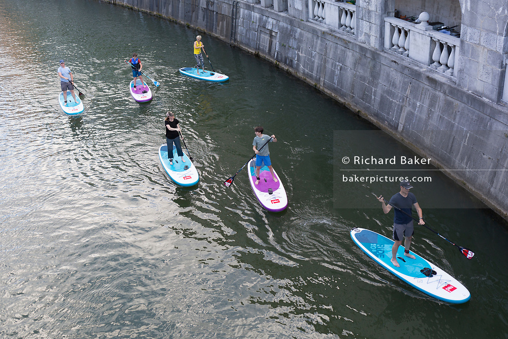 Flat boarders paddle down the Lubljanica river in the Slovenian capital, Ljubljana, on 25th June 2018, in Ljubljana, Slovenia.