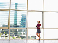 Businesswoman by window in office building portrait
