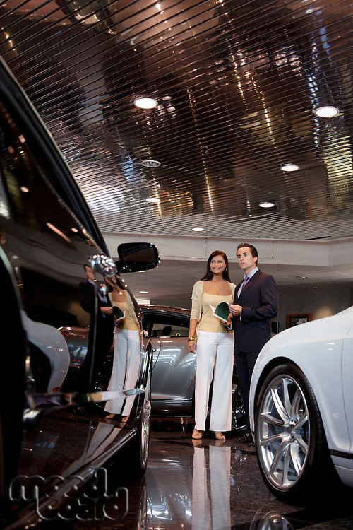 Woman standing with auto salesman in showroom