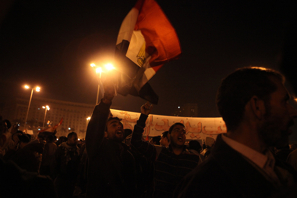 Pro-democracy protesters chant and hold up their shoes after watching a televised speech by Hosni Mubarak when the then president refused to step down on 1 February.