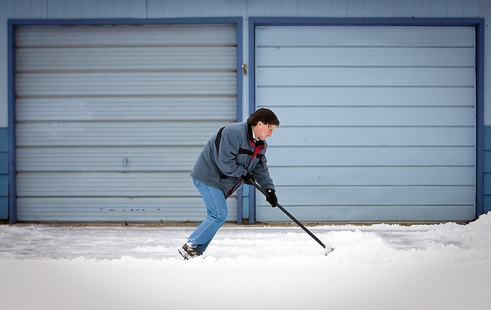 JEROME A. POLLOS/Press..Bill Buley shovels an old lady's driveway after he interviewed her for a story about ElderHelp delivering Christmas boxes to those in need. Despite him saying that he was only going to do a little and then let the ElderHelp volunteer finish, he ended up doing most of the driveway.