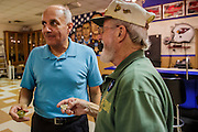 02 AUGUST 2012 - PHOENIX, AZ: Dr RICHARD CARMONA (blue shirt) talks to a Special Forces veteran of the Vietnam War during a campaign stop at an American Legion Hall in Phoenix Thursday. Carmona, the former US Surgeon General under President George W. Bush, is running for the US Senate as a Democrat. Carmona's personal story is an important part of his campaign. He dropped out of high school to join the US Army. He applied for Special Forces and was turned down because he didn't have a high school diploma, he got his GED, reapplied and was accepted into Special Forces. He served in Vietnam as a combat medic. After he was discharged, he went back to college, became a R.N., went to medical school and became a surgeon, became a police officer and member of the SWAT Team in Tucson, AZ. He became the surgeon general in 2002 and returned to Tucson after his term as surgeon general.     PHOTO BY JACK KURTZ