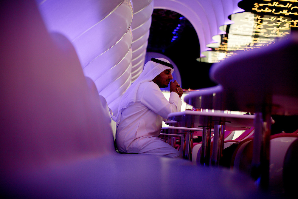 A young man in a resturant at the Dubai Mall.. .The Dubai Mall is the world's largest shopping mall based on total area and sixth largest by gross leasable area. Located in Dubai, United Arab Emirates, it is part of the Burj Khalifa complex, the 20-billion-dollar project has 1,200 shops...Photo by: Eivind H. Natvig/MOMENT