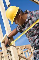 Construction worker measuring half constructed wall with tape measure