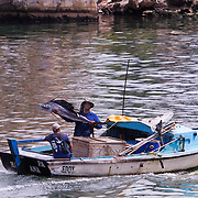 A proud fisherman shows off a marlin caught on the waters off Havava. The small fishing boat motor into port on the River Almendares. Fishing is not only a favorite pastime for Cubans but it is also an income source.   Photography by Jose More