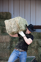 cowboy with a bale of hay on his shoulder