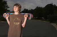 Teenage boy (13-15) holding skateboard standing on street