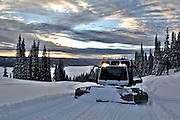 USA, Idaho, Valley County, Donnelly, Tamarack Resort, A snow cat grooms the road to the top of West Mountain at dawn