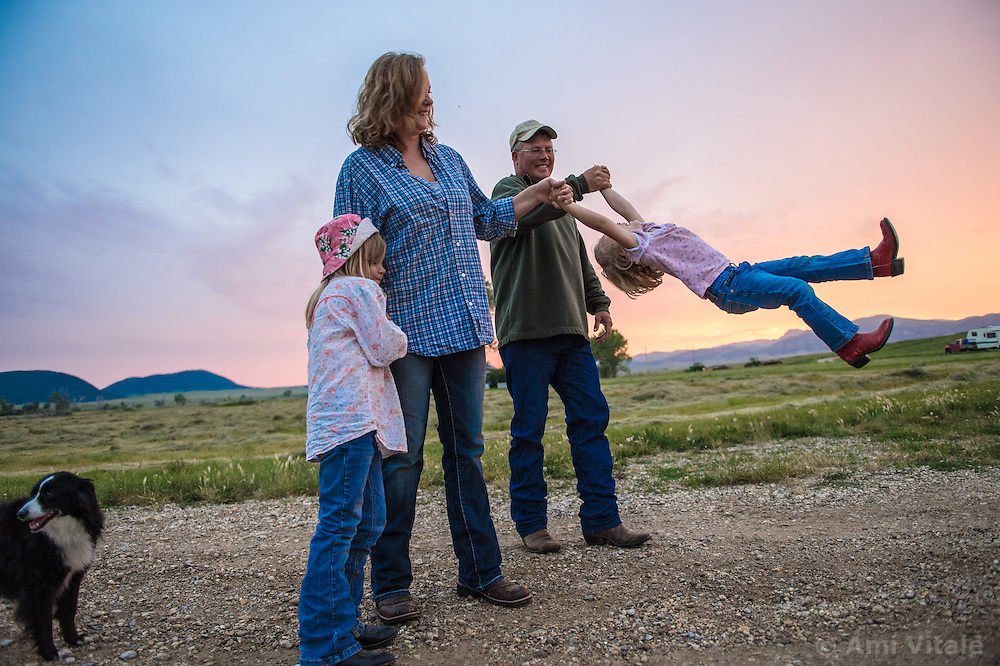 The Nature Conservancy's Matador Ranch Operations Manager Charlie Messerly, his wife Jolynn and daughters Layla, 5, and Janae relax after a long day working with  ranching families in Eastern Montana  at the Matador ranch &quot;grass bank&quot;. The &ldquo;grass bank&quot; is an innovative way to leverage conservation gains, in which ranchers can graze their cattle at discounted rates on Conservancy land in exchange for improving conservation practices on their own &ldquo;home&rdquo; ranches. In 2002, the <br /> Conservancy began leasing parts of the ranch to neighboring ranchers who were suffering from  severe drought, offering the Matador&rsquo;s grass to neighboring ranches in exchange for their  participation in conservation efforts. The grassbank has helped keep ranchers from plowing up native grassland to farm it; helped remove obstacles to pronghorn antelope migration; improved habitat for the Greater Sage-Grouse and reduced the risk of Sage-Grouse colliding with fences; preserved prairie dog towns and prevented the spread of noxious weeds. (Photo By Ami Vitale)
