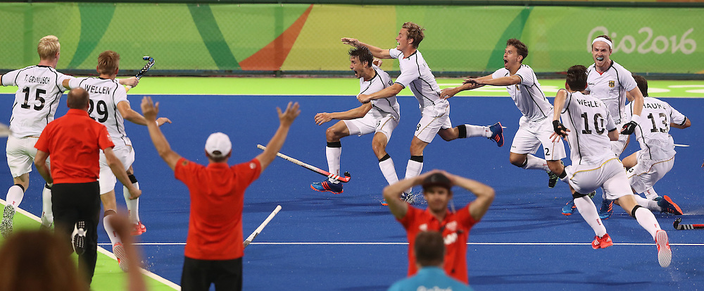 RIO DE JANEIRO, BRAZIL - AUGUST 14:  Florian Fuchs of Germany is mobbed by team mates  after scoring the match winning last second goal during the Men's hockey quarter final match between the Germany and New Zealand on Day 9 of the Rio 2016 Olympic Games at the Olympic Hockey Centre on August 14, 2016 in Rio de Janeiro, Brazil.  (Photo by David Rogers/Getty Images)