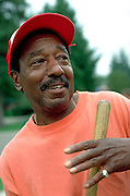 African American age 71 leader and volunteer repairing little league ballpark.  St Paul  Minnesota USA