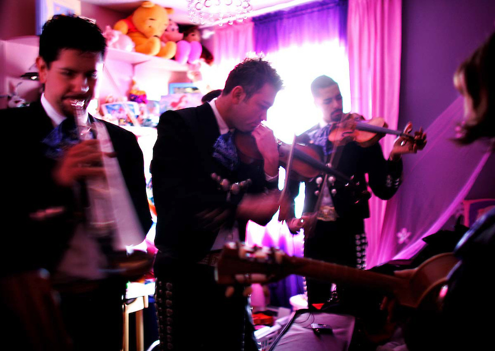 Trumpet player Timoteo Serna, left, and violinist Charles Garcia, right, warm up their instruments on either side of Mariachi Orgullo de Nuevo Mexico founder Adan Branchal. The group prepares in a child's room at the Martinez home before performing at a Baptismal celebration. (Xavier Mascareñas)