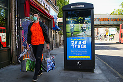 © Licensed to London News Pictures. 12/05/2020. London, UK. A shoppers wearing a face covering walks past a 'STAY ALERT TO STAY SAFE' billboard in north London, which is a part of the government's new public information campaign as the lockdown is gradually eased. Photo credit: Dinendra Haria/LNP