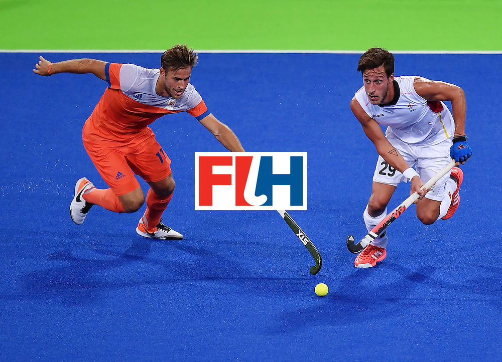 Netherland's Jeroen Hertzberger (L) vies with Belgium's Elliot van Strydonck during the men's semifinal field hockey Belgium vs Netherlands match of the Rio 2016 Olympics Games at the Olympic Hockey Centre in Rio de Janeiro on August 16, 2016. / AFP / MANAN VATSYAYANA        (Photo credit should read MANAN VATSYAYANA/AFP/Getty Images)