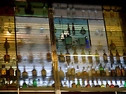 spirit bottles seen from behind through frosted glass