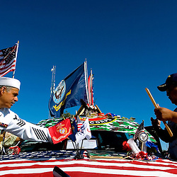 090207      Brian Leddy.Damon Eli and Emery Romancito, both veterans of the Navy, arrange decorations on the hood of a truck commemorating military personnel prior to the start of the 43rd Annual Zuni McKinley County Fair parade on Sunday morning. They lined the vehicle with dozens of photographs and flags in honor of the holiday.