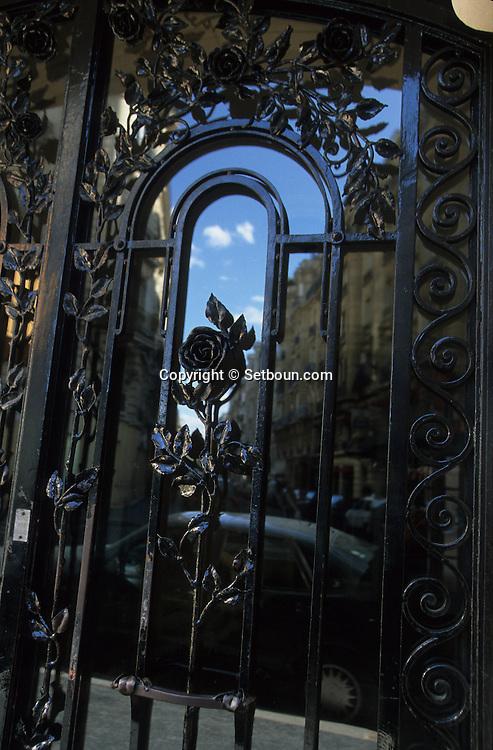 France. Paris. 7th district. door with roses / 105-107 rue de Sèvres       / Porte fer forgé 105-107 rue de Sèvres (pleine de roses).