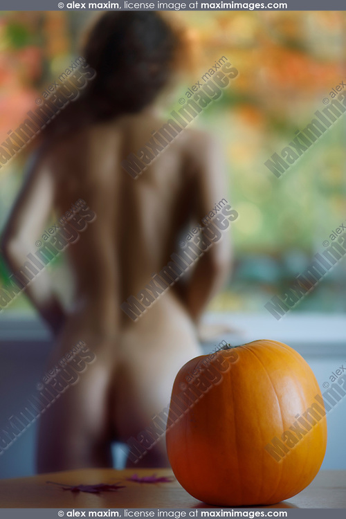 Cute artistic portrait of a blurred back silhouette of a nude woman standing by the window naked looking at fall nature scenery with a pumpkin on the table