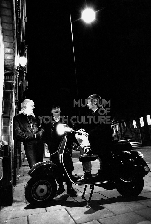Three skinhead women in the street, one sitting on a moped