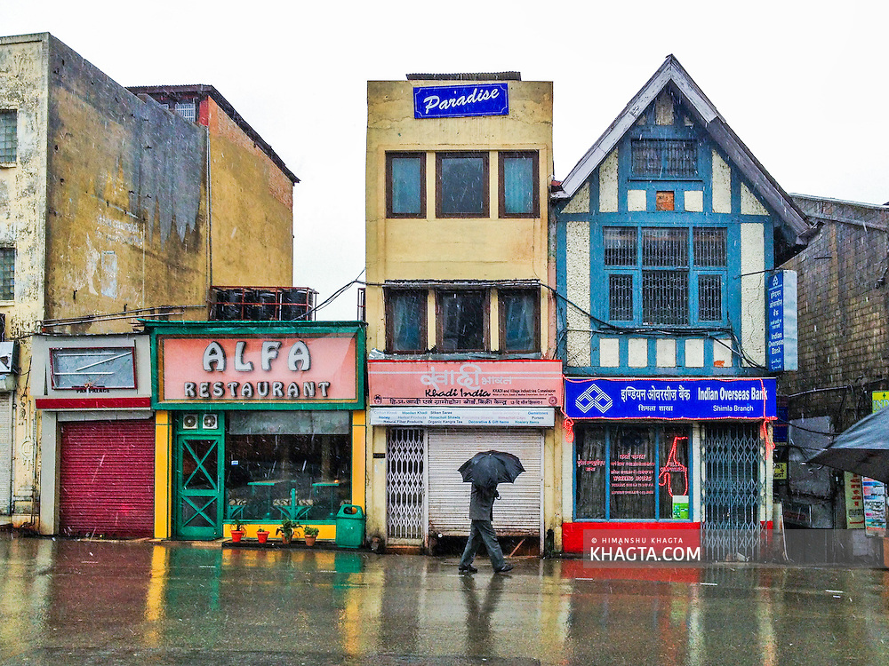 A man walks by a closed shop at Scandal Point on the mall road of Shimla during the first snowfall of the 2014 season.