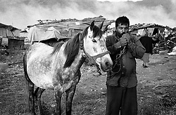 A man and his horse at the end of the day. In the background you can just see Montenegro's mountains and the smoke from the garbage dumps next to the large refugee camp. ..Konik camp, Montenegro.