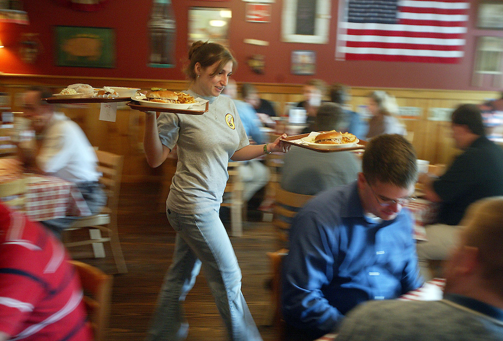 Kerri Carriero rushes trays of food out to customers during lunch hour at Slopes BBQ in Sandy Springs.