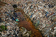 Seepage from a garbage dump in the industrial north of Chennai, finds its way into a storm drain, which will take this water to the Buckingham Canal that will finally deliver its contaminants into the Bay of Bengal and into the fish that are caught for market.  Chennai, India.