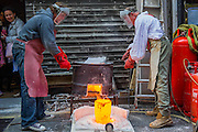 Molten metal is moved and poured - Nic Fiddian-Green (pictured in white shirt with Chris Nash the owner of the foundry he uses) sets up his iron foundry in Bruton Place, Mayfair to demonstrate the ancient art of 'lost wax' casting and also hand patinating. A sculptor of monumental neo-classical horses heads, he also has a new solo show at Sladmore Contemporary from 10th June until 31st July 2015. The exhibition will include a recreation of the artist's hilltop surrey studio and workshop,  with new work in  progress.