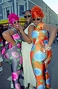 Three women in bright clothing and wigs pose for the camera, Notting Hill Carnival, 1996.