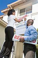 Two people putting up notice outside house