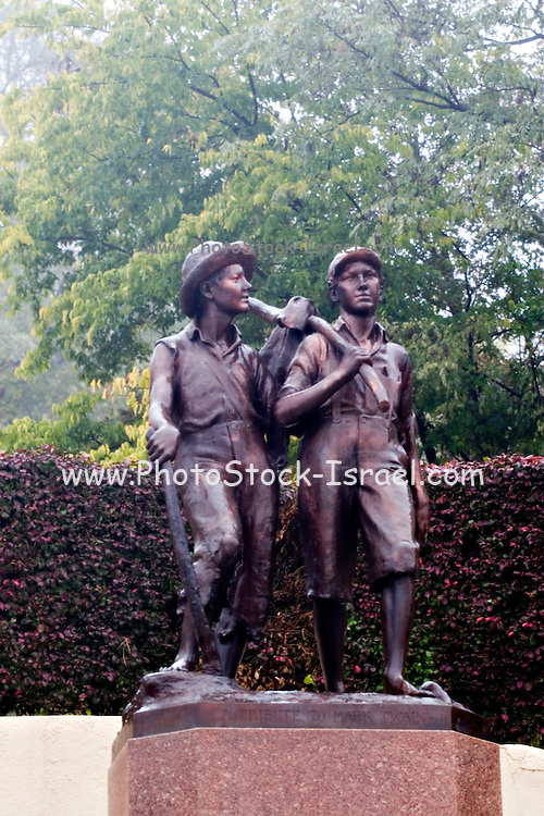 USA Missouri MO, Hannibal a port town on the Mississippi River better known as the childhood town of Samuel Langhorne Clemens AKA Mark Twain. A statue of Huckleberry Finn and Tom Sawyer at the bottom of Cardiff Hill (the hill from the stories where Tom and Huck played)