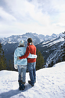 Couple looking at view from mountain peak back view