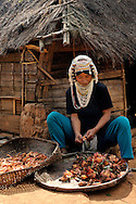 Burma/Myanmar. Akha woman working near her house.