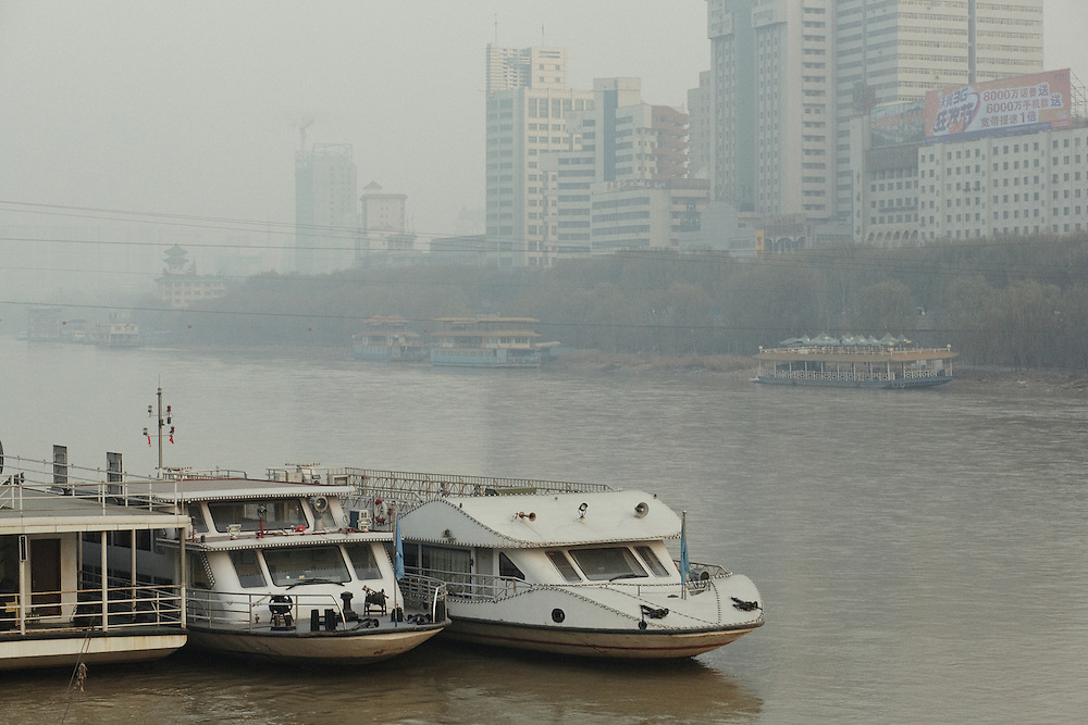 Lanzhou, along the Yellow River. The density of the pollution is sometimes so high that the other riverside almost disapears. <br /> <br /> -------<br /> Lanzhou, in the Gansu province is one of the most polluted cities of China and in the world's top ten for atmospheric pollution due to human activity. The town is situated between two hills along the Yellow River and the polluted clouds remain blocked over the town. The sky is most of the time hidden by the pollution.