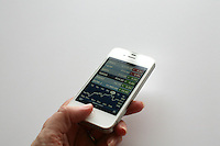 Person using a white iPhone 4s to read stock report updates