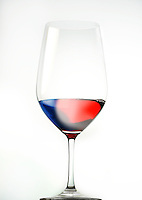 Glass of red wine with french flag colors on white background