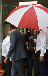 Premier League footballer Andy Carroll (back and obscured by umbrella) leaves Barkingside Magistrates' Court after he re-attended court after a last-minute request for him to give further evidence in the trial of a man accused of trying to rob him of his £22,000 watch.