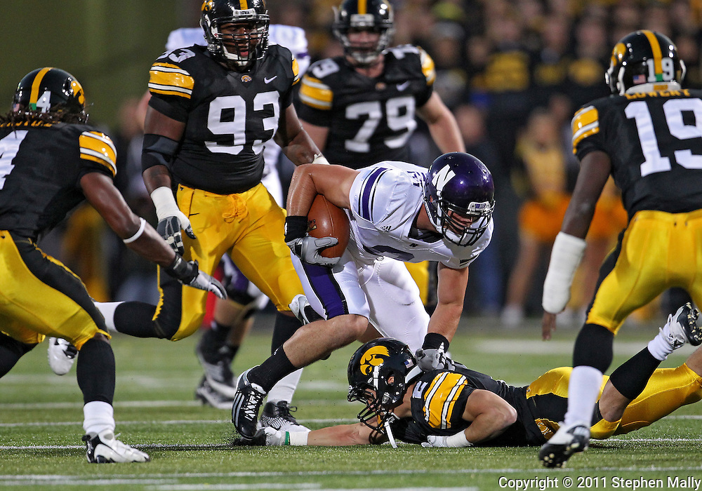 October 15, 2011: Northwestern Wildcats tight end Drake Dunsmore (9) tries to avoid Iowa Hawkeyes defensive back Greg Castillo (2) during the first half of the NCAA football game between the Northwestern Wildcats and the Iowa Hawkeyes at Kinnick Stadium in Iowa City, Iowa on Saturday, October 15, 2011. Iowa defeated Northwestern 41-31.