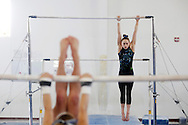 Rachel Gowey, 18, of Urbandale leads off warm up drills hangs from the uneven bars Thursday, May 12, 2016, during a mid morning practice at Chow's Gymnastics and Dance in West Des Moines before heading back to school.