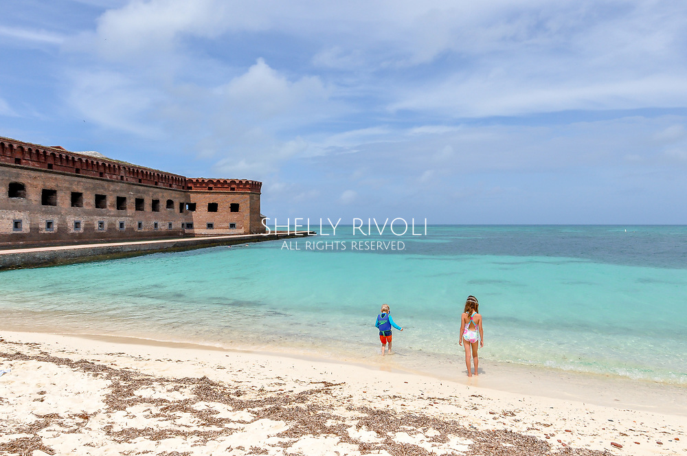 Kids play on the white sand beach at Dry Tortugas National Park. The children wade into the clear water by the beach with Fort Jefferson in the distance. Dry Tortugas is known as a family travel bucket list destination. Model released photo.