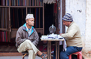 A tailor and his friend sit outside his shop in conversation while he sews.