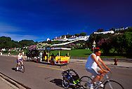 BICYCLISTS AND HORSE-DRAWN CARRIAGES TRAVEL THE STREETS OF MACKINAC ISLAND, MICHIGAN BELOW FORT MACKINAC.
