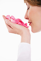 Woman smelling pink rose petals in hand