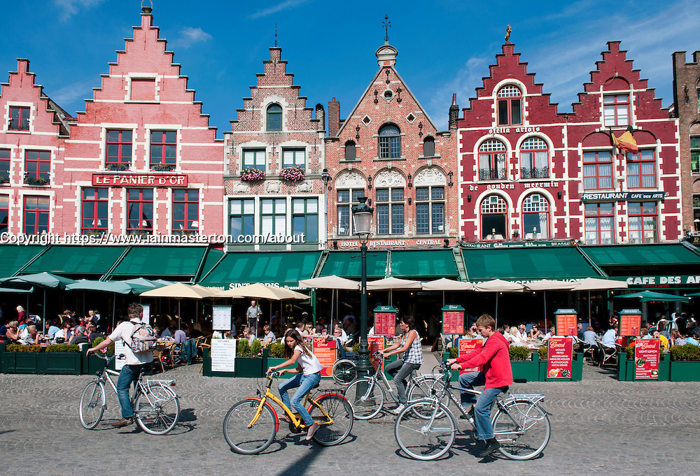Row of ornate historic buildings and restaurants  in Market Square in Bruges in Belgium