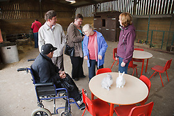 Carer showing rabbits to people with learning disability on trip to farm