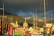 Historic buildings in the Torget market square area of Vagen harbour, Bergen, Norway dark rain clouds