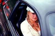 A girl sat in her car, wearing gold jewellery and a hat, Girlracers, Southend, UK 2004