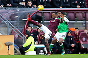 Arnaud Djoum (#10) of Heart of Midlothian clears the ball over his own head under pressure from Efe Ambrose (#25) of Hibernian during the William Hill Scottish Cup 4th round match between Heart of Midlothian and Hibernian at Tynecastle Stadium, Gorgie, Scotland on 21 January 2018. Photo by Craig Doyle.