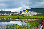 Songzanlin Tibetan Buddhist Monastery reflected in sacred lake, Shangri-La, Yunnan Province, China